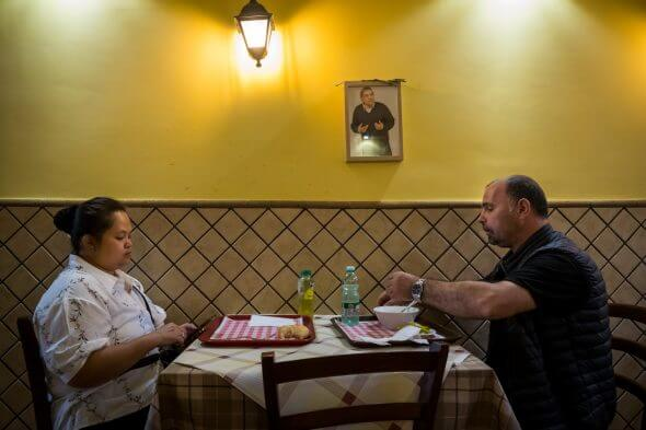 """Preotul și soția lui mănâncă la un împinge-tava românesc, care se numește """"Tavola Calda La Mama"""", unde toți angajații și majoritatea clienților sunt români."""